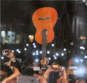 La chitarra, in una piazza gremita da 100 000 persone, esibita a mo' di fazzoletto da Domenico mio figlio nel momento del saluto (foto dal Mattino di Napoli)